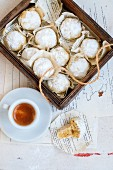 Walnut cookies covered in icing sugar and served with an espresso