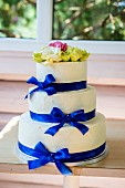 A three-tiered buttercream wedding cake with blue silk ribbons