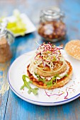 A fish burger with pink sauce and bean sprouts