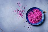 Ungekochter rosafarbener und schwarzer Reis auf Teller vor grauem Hintergrund