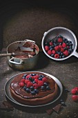 Chocolate cake with fresh berries and chocolate cream, served with vintage kitchenware over dark background