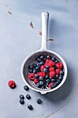 Aluminium colander with fresh raspberries and blueberries over gray metal background
