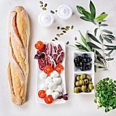 Antipasti: Baguette, Salami, Mozzarella, Tomaten und Oliven (Aufsicht)