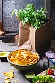 Mexican style dinner with tortilla, herbs, corn chips nachos and guakomole, served over gray wooden table