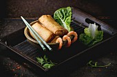 Fried spring rolls with vegetables and shrimps, served in ceramic bowl with chopsticks
