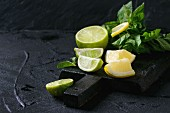 Sliced Lime and lemons with bunch of fresh mint on black wooden chopping board over black textured background
