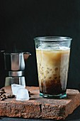 Glass of ice coffee with cream and milk, served with coffee beans, ice cubes and coffee pot on stone board