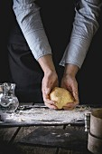 Female hands hold ready-made dough for pasta on old wooden kitchen table, powdered by flour