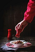 Female hand throws salt from red salt cellar into vintage english plate of homemade pasta pici with Bolognese sauce