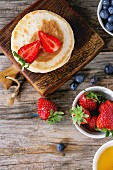 Pancakes with strawberries and blueberries, bowls of honey and fresh berries over old wooden background