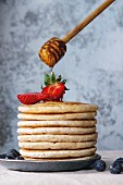 Pancakes with fresh strawberries and blueberries and flowing honey from wooden honey dipper