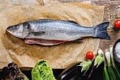 Raw uncooked seebass fish on baking paper with sea salt, dry herbs and vegetables