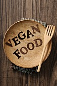 'Vegan Food' written on a wooden plate with a fork