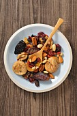 Dried fruit and nuts in a bowl with a wooden spoon