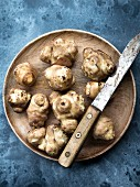 Jerusalem artichokes on a wooden plate with a knife