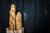Homemade malt baguettes in a paper bag