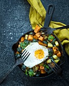 Pan fried sweet potatoes with brussels sprouts, fried egg and parsley