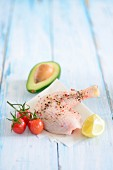 A spiced chicken leg with cherry tomatoes, lemon and avocado