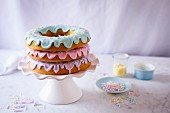 A doughnut cake with three pastel coloured glazes