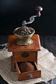 Alte Kaffeemühle mit Kaffeebohnen und Pulver