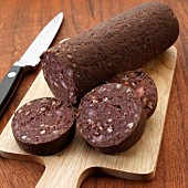 Uncooked English black pudding on cutting board with knife