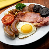 Full English, Irish breakfast with egg, bacon, bangers, black pudding, white pudding fried potatoes, tomato