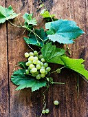 Green grapes with vine leaves on a wooden background
