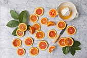 Orange slices with a citrus press on a marble background