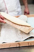Unbaked French baguette on a wooden board
