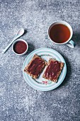 Tahini and raspberry jam on crisp bread and a cup of tea