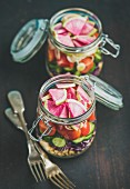 Healthy take-away lunch jars: vegetable and chickpea sprout vegan salad in glass jars