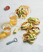 Healthy corn tortillas with grilled chicken fillet, avocado, fresh salsa, limes, beer in glasses