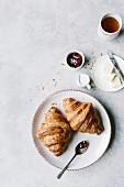 Zwei Croissant mit Butter, Marmelade und Tee auf weißem Untergrund