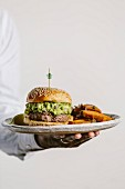 A man is holding a plate of guacamole burger and sweet potato fries