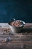 Raw hazelnuts in a metal bucket on a wooden table