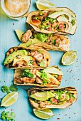 Healthy corn tortillas with grilled chicken, avocado, fresh salsa, limes and beer in glass