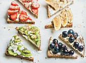 Healthy breakfast wholegrain bread toasts with cream cheese, various fruit, seeds and nuts, top view