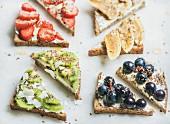Gesundes Frühstück: Toastecken verschieden belegt mit Früchten und Kernen
