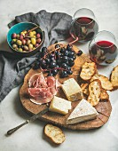 Variety of cheese, olives, prosciutto, roasted baguette slices, grapes on wooden board and glasses of red wine