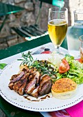 Grilled duck breast with rosemary and salad on a restaurant table