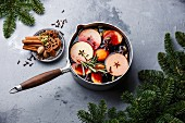 Mulled wine hot drink with citrus, apple and spices in aluminum casserole and Fir branch