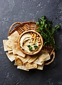Homemade hummus with pita chips and parsley on black stone background copy space