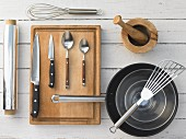 Kitchen utensils: mortar, pan, spatula, aluminium foil, whisk, knives
