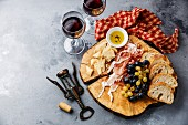 Appetizer plate with prosciutto, parmesan cheese, bread and wine on gray concrete background