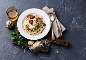 Risotto with porcini mushrooms on dark stone background