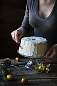 Woman is frosting a chiffon cake on wooden table