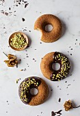 Donuts with chocolate and pistachios on marble table