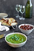 Arugula Chive Basil Pesto served in a ceramic bowl with crostini, almonds and wine