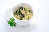 Couscous with olives and parsley in a takeaway cup