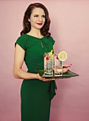 A woman holding a tray of Tom Collins cocktails